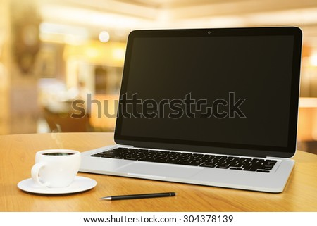 laptop with blank screen on a wooden table with cup of coffee and pen - stock photo