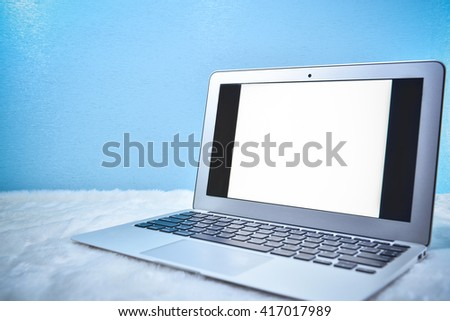 Laptop with blank screen on blue - stock photo