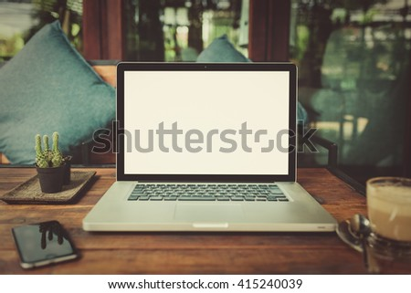 Laptop with blank screen on table. laptop computer on wood table. gray color laptop. laptop white screen. laptop and smartphone on table. laptop and coffee cup in cafe. laptop vintage tone. - stock photo