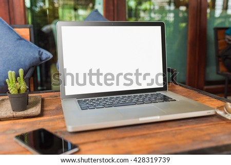 Laptop with blank screen on table. laptop computer on wood table. gray color laptop. laptop white screen. laptop and smartphone on table. laptop and coffee cup in cafe. laptop vivid tone. - stock photo