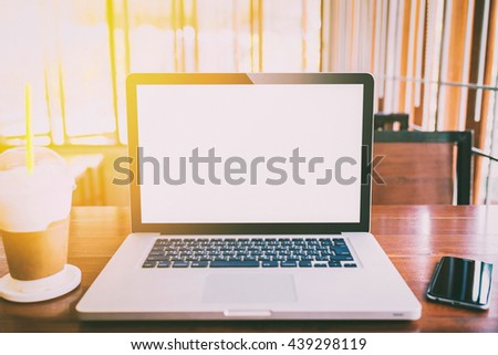 Laptop with blank screen on wood table. gray color laptop white screen and smartphone and coffee cup in cafe vintage tone. - stock photo