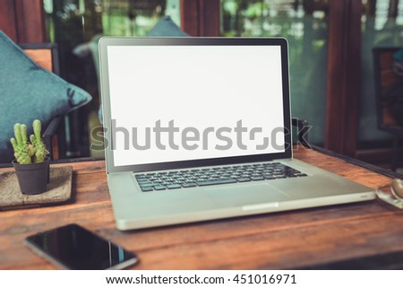 Laptop with blank screen on wood table. gray color laptop white screen and smartphone on table vintage tone. - stock photo