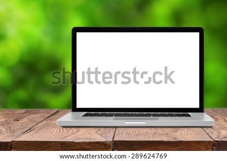 Laptop with blank screen on wooden empty brown table on green natural summer blurred background - stock photo