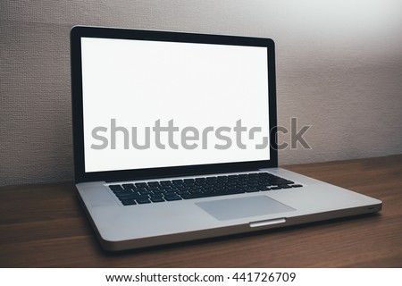 Laptop with blank screen on wooden table - stock photo