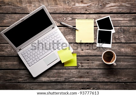 Laptop with coffee cup, instant photos and sticky note paper with notepad on old wooden table.