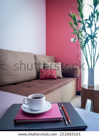 Laptop with coffee cup on couch in bright modern Living room