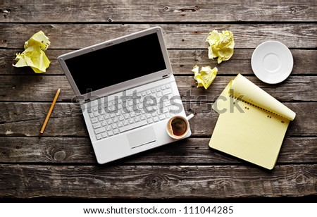 Laptop with crumpled paper, blank notepad and pencil on old wooden table. Workplace writer. - stock photo