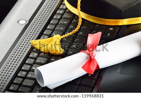 Laptop with diploma and graduation cap - stock photo