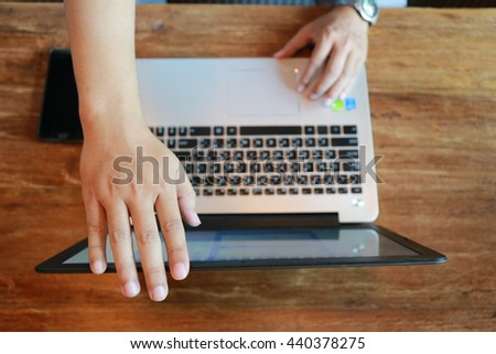 Laptop with hand working on old wooden table - stock photo