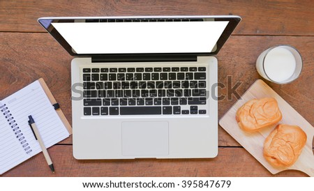 laptop with notebook ,bread and cup of milk on wooden table background.