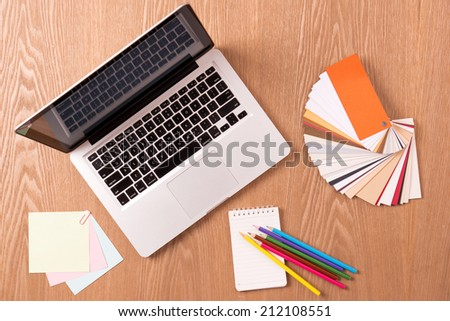 Laptop with office supplies and color swatches on old wooden table. Workplace designer. A concept of architecture design - stock photo
