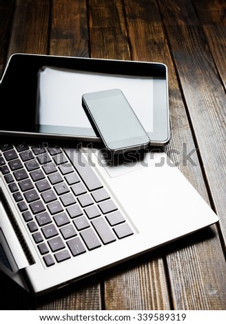 Laptop with phone and tablet pc on wooden desk  - stock photo