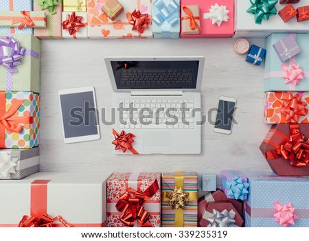 Laptop with ribbon, tablet, smartphone and plenty of gifts on a wooden table, top view, celebrations and Christmas concept - stock photo