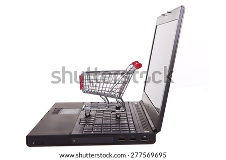 Laptop with small shopping cart isolated in white - stock photo