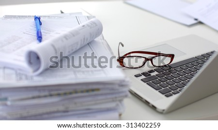 Laptop with stack of folders on table on white background - stock photo
