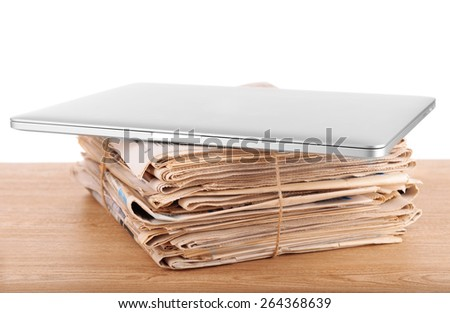 Laptop with stack of newspapers on table on white background - stock photo