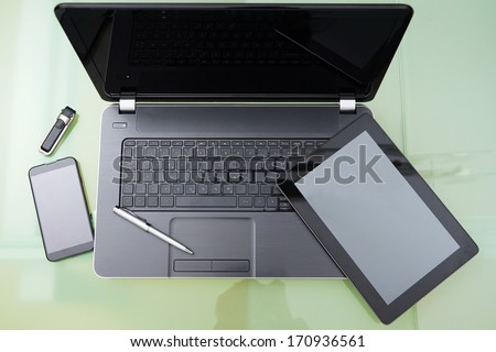 laptop with tablet and  smart phone on glass table - stock photo