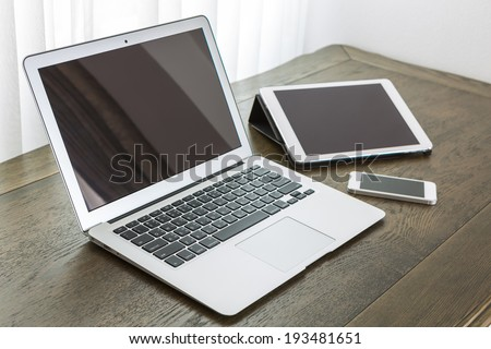 laptop with tablet and smart phone on table - stock photo
