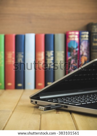 Laptop with USB flash drive. Several books on the background