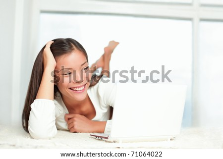 Laptop woman at home smiling at PC screen laughing. Casual Asian / Caucasian young woman lying on the floor looking at the computer - stock photo
