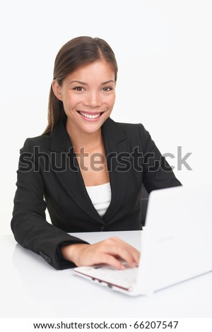 Laptop woman smiling looking at camera. Young happy businesswoman sitting at table with computer. Asian / Caucasian model.
