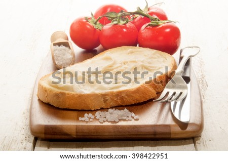 lard bread on wooden board with coarse salt and tomatoes - stock photo