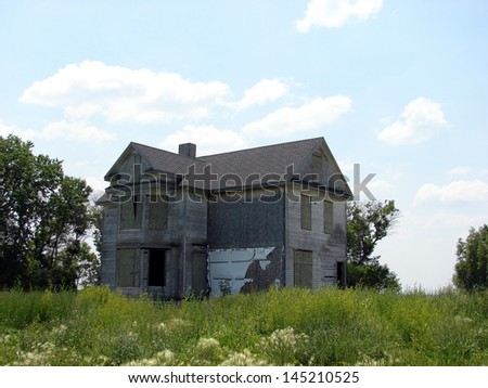 large abandoned farm house on a hilltop - stock photo
