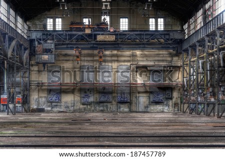 Large abandoned hall with an old crane - stock photo