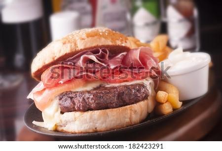 Large, abundant and tasty Hamburger with french fries - stock photo
