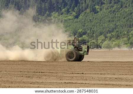 Large agricultural tractor smoothing out a tilled field with a disc implement preparing for planting - stock photo