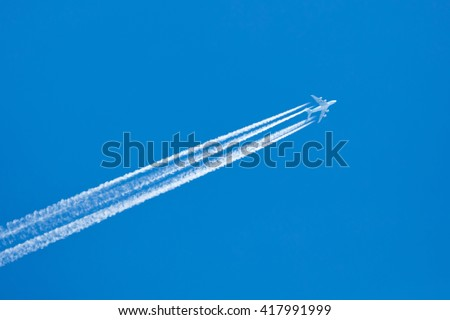 Large aircraft flying in sky, 4 stripes in the sky - stock photo