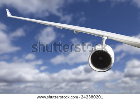 Large Airplane Wing Against Blue Sky and Clouds.