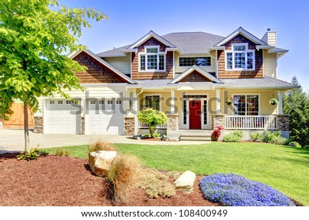 Large American beautiful house with red door and two white garage doors. - stock photo
