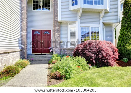 Large American  grey house with red door. - stock photo
