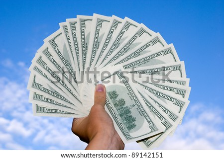 Large american hundred dollars fan in the hand against the blue sky - stock photo