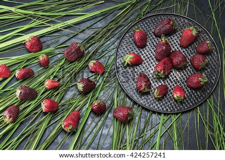 Large and delicious strawberries, laid out on a black iron plate - stock photo