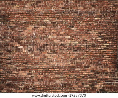 large and detailed brick wall, with multicolor bricks, and some splashes of white paint - stock photo