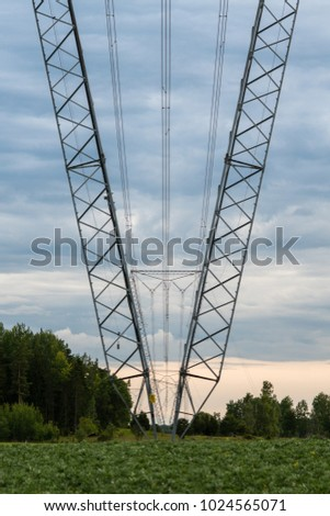 Large and high towers with power lines distributing 400 kV of energy from a powerplant, passing a green environment with blue and gray evening sky