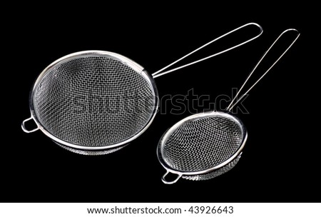 Large and small metal sieve on a black background