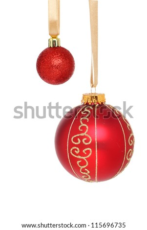 Large and small red Christmas baubles hanging from gold ribbons isolated against white