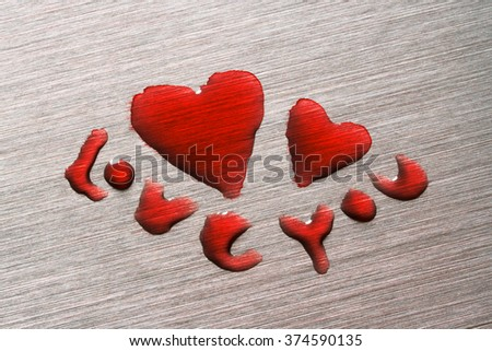 Large and small red hearts on a metal surface with the words love you