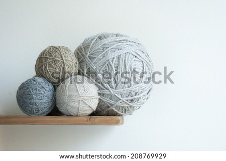 large and small size balls of wool on desk - stock photo