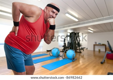 Large and tired fitness man with back pain - stock photo