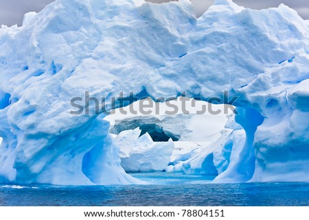 Large Arctic iceberg with a cavity inside - stock photo