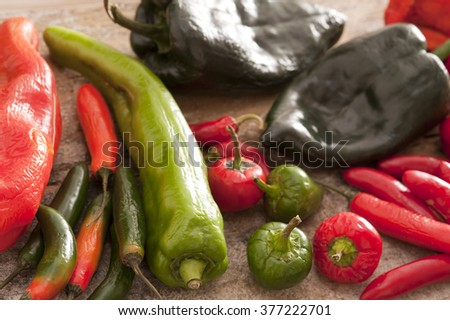 Large assortment of hot chili peppers or capsicum with jalapeno, cayenne, red, green and black peppers arranged on a kitchen table - stock photo