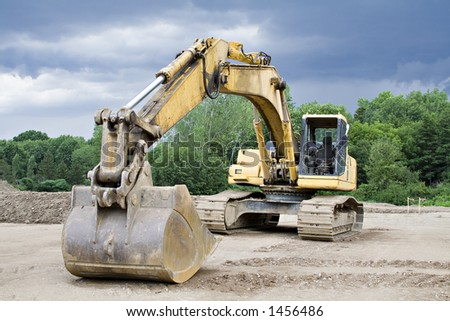 Large Back Hoe against a stormy sky - stock photo
