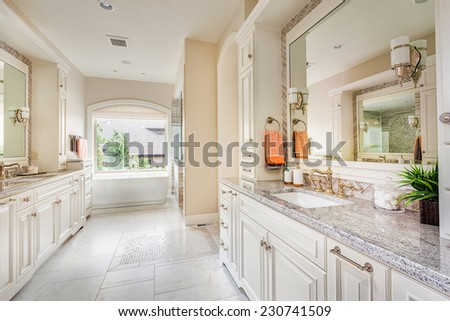 Large bathroom interior in luxury home with two sinks, tile floors, fancy cabinets, large mirrors, and bathtub - stock photo