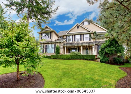Large beautiful home with green grass - stock photo