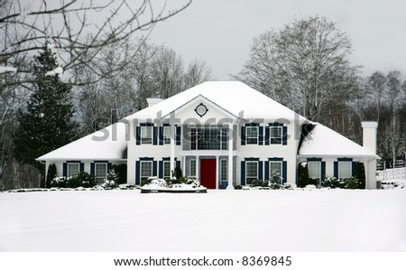 Large beautiful house in the snow, front door is red.
