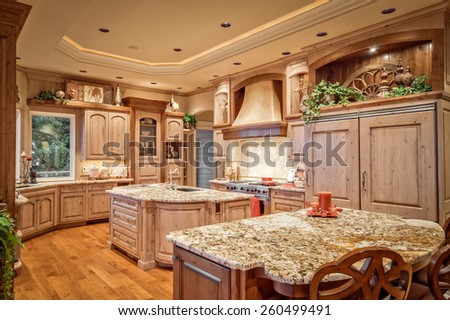 Large, Beautiful Kitchen in New Luxury Home with Sink, Oven and Range with Hood, Hardwood Floors and Tray Lighting - stock photo